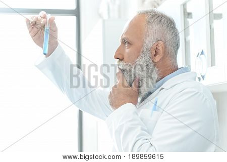 Senior Bearded Scientist In White Coat Thinking And Looking At Tube With Reagent In Chemical Lab