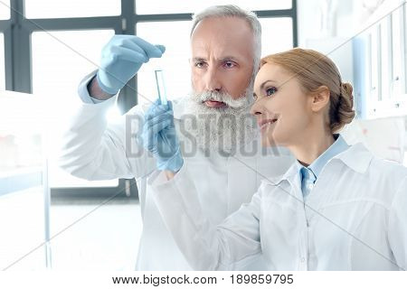 Two Caucasian Chemists In White Coats Looking At Tube In Chemical Laboratory