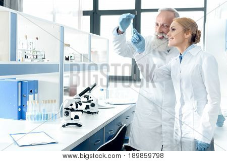 Two Smiling Chemists In White Coats Looking At Tube In Chemical Laboratory With Microscopes