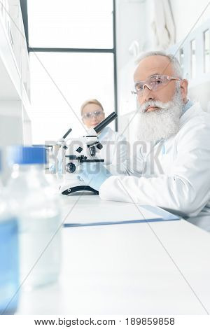 Professional Chemists In White Coats Working With Microscopes In Laboratory And Looking At Camera