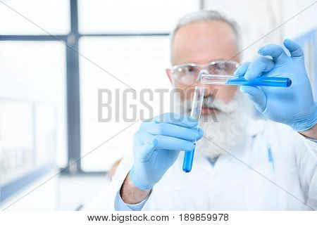 Serious Bearded Scientist In Protective Goggles And Gloves Holding Test Tubes With Reagents And Maki