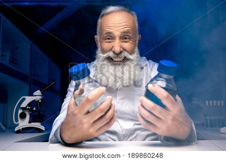 Portrait Of Happy Scientist Looking At Bottles With Reagents In Hands In Laboratory