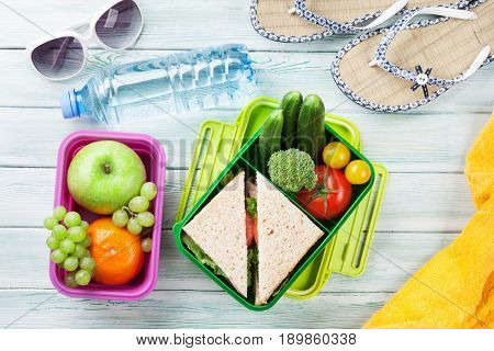 Lunch box with vegetables and sandwich on wooden background. Beach take away food box, towel and glasses. Top view