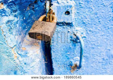 Obsolete blue metal door locked with padlock