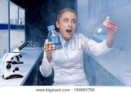 Portrait Of Excited Scientist Working With Reagent In Flask In Laboratory