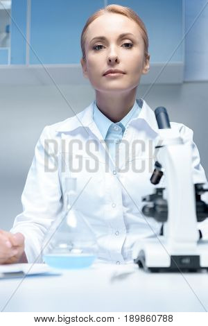 Portrait Of Confident Scientist In White Coat Sitting At Workplace In Laboratory