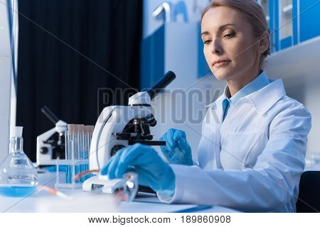 Portrait Of Focused Scientist Using Microscope While Working With Reagents In Lab