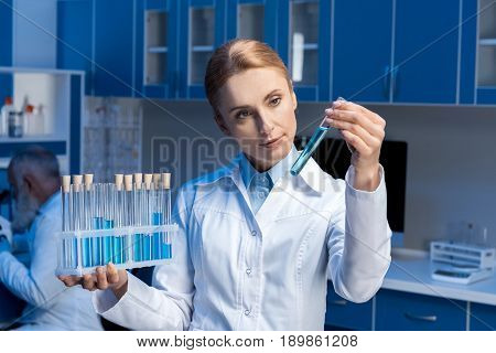 Pensive Scientist In Lab Coat Looking At Tube At Laboratory