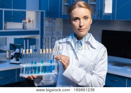 Scientist Looking At Camera And Holding Tubes With Reagents At Laboratory