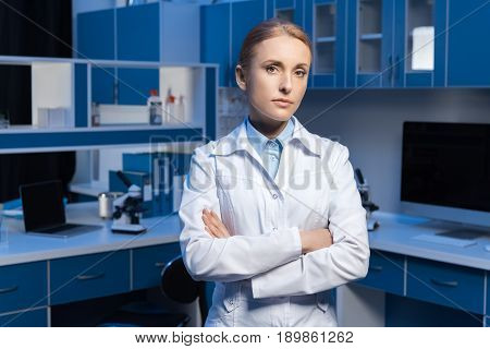 Confident Scientist In Lab Coat Looking At Camera With Arms Crossed