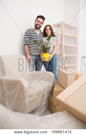 Relocating, yong couple standing in new apartment with furniture coverd with foil. Happy man and woman standing in newly bought apartment.
