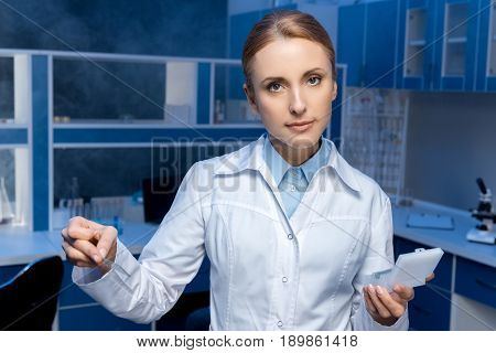 laboratory technician in lab coat looking at camera at laboratory