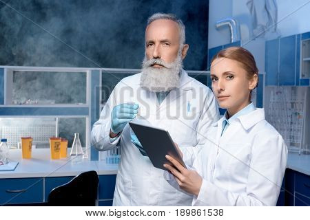 Pensive Laboratory Technicians In Lab Coats Looking At Camera At Laboratory