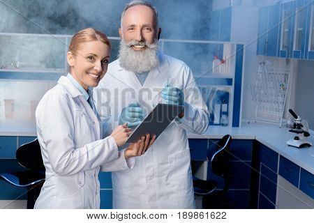 Colleagues In Lab Coats Using Digital Tablet During Work At Laboratory