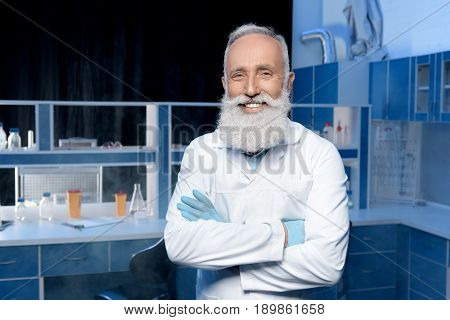 Smiling Grey Haired Scientist In Lab Coat Looking At Camera With Arms Crossed