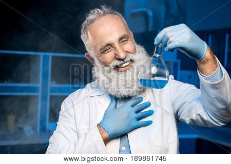 Happy Mature Scientist In Lab Coat Holding Flask With Reagent At Laboratory