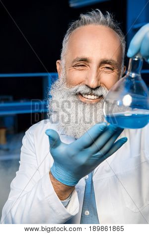 Happy Grey Haired Scientist In Lab Coat Holding Flask With Reagent At Laboratory