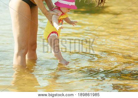 Sweet little baby in parent hands in lake water. Babyhood and parenting.