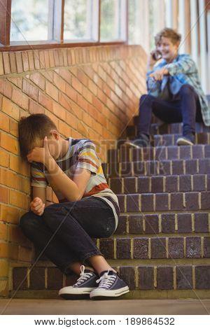 School friend bullying a sad boy in school corridor at school