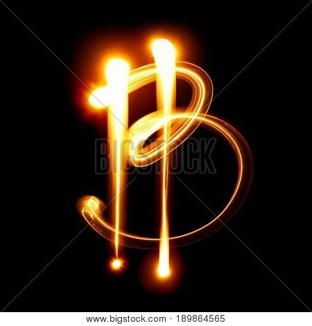 Bitcoin sign over black background. Light drawing