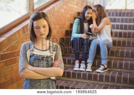 School friends bullying a sad girl in school corridor at school