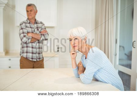 Worried senior couple ignoring each other in kitchen