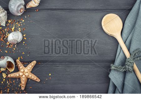 Seashellswooden spoon and dish towel on the blue wooden background. Top view. Copy space