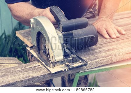 Male hand cuts with a circular saw a piece of Board on a Sunny day close-up. Toned. A horizontal frame.
