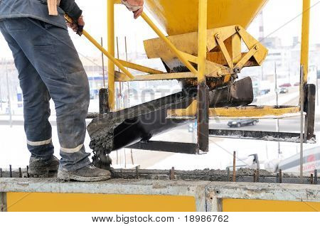 construction building worker at construction site pouring concrete in a form