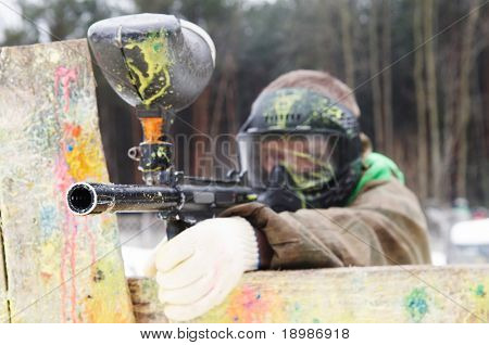 paintball sport player with mask aiming gun and shooting to enemy in winter