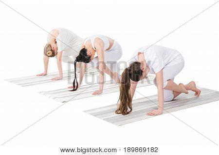 Women Performing Knee To Forehead Asana Or Eka Pada Marjariasana On Yoga Mats Isolated On White