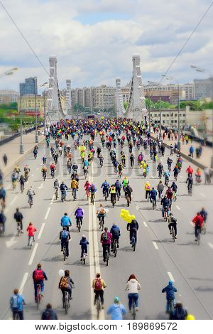 City bike festival. Mass urban cycling marathon. Cyclists go to the bridge, back to us. Concept of modern lifestyle, healthy lifestyle. Selective focus. Vertical