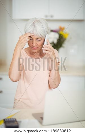 Tensed senior woman talking on mobile phone in kitchen at home