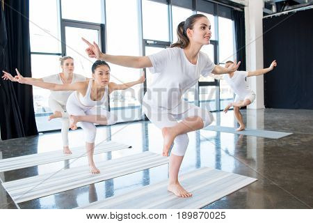 Girls Doing Golden Rooster Stands On One Leg Yoga Stance With Instructor Indoors