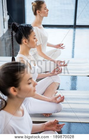 Multiethnic Women With Eyes Closed Meditating In Lotus Pose With Gyan Mudra Indoors