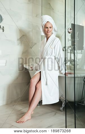 Full length of a beautiful young woman in bathrobe and towel on her head sitting on a bathtub