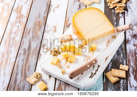 Delicious dutch gouda cheese with cheese blocks, crackers, walnuts and special knife on oud wooden table. Copy space.
