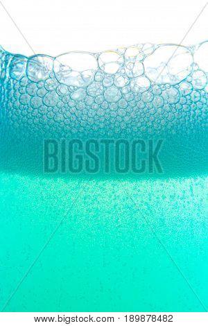 Blue foam bubbles liquid water background close up