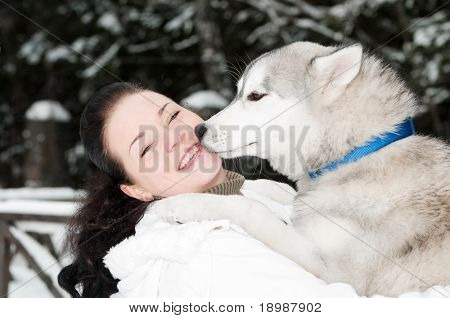 happy positive siberian husky owner facing to dog snout at winter outdoors poster