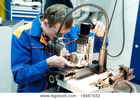 worker in uniform checking quality of countersink reamer sharpening using precise optical device