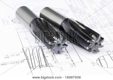 Two finished metal reamer tools with protective coating lying on blueprint drawing