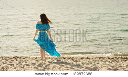 Young beautiful woman on the beach in azure long dress. Selective focus.