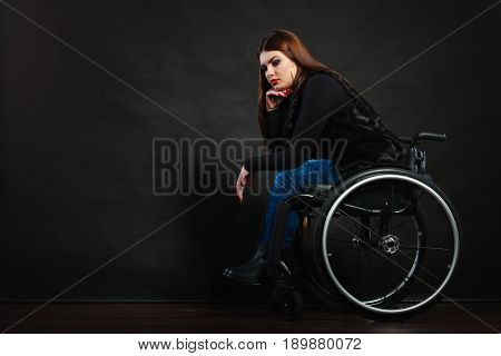 Disability sadness disease tragedy concept. Sad girl on wheelchair. Crippled young gorgeous lady casually dressed sitting on mobile chair.