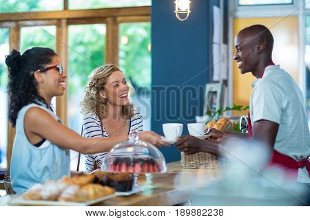 Waiter serving coffee to female customers in café