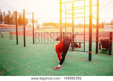 The girl on the sports field stretches the muscles of her legs and back the twine. The concept of a healthy lifestyle and exercises to strengthen the hands and back and joints.