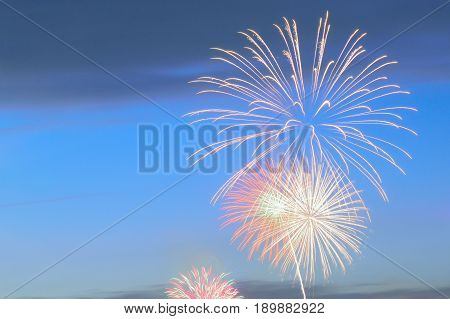 Holiday colorful fireworks background at dusk in horizontal frame