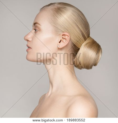 Portrait Of Beautiful Young Blond Woman With Bun Hairstyle.