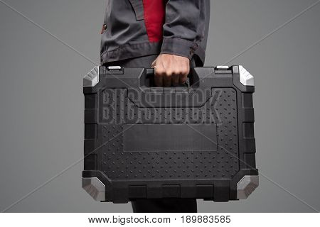 Serviceman holding black case with instruments. Gray background.