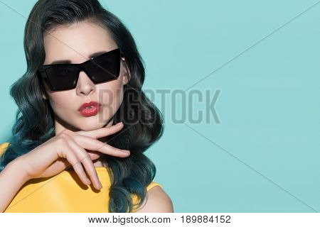 Fashion portrait of stylish woman in sunglasses. On a blue background.