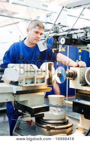 worker in uniform working on sharpening machine tool